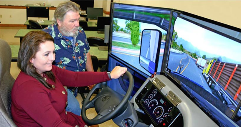 Kelly Strunk puts the CDL simulator through its paces as program coordinator John Mitchell looked on.